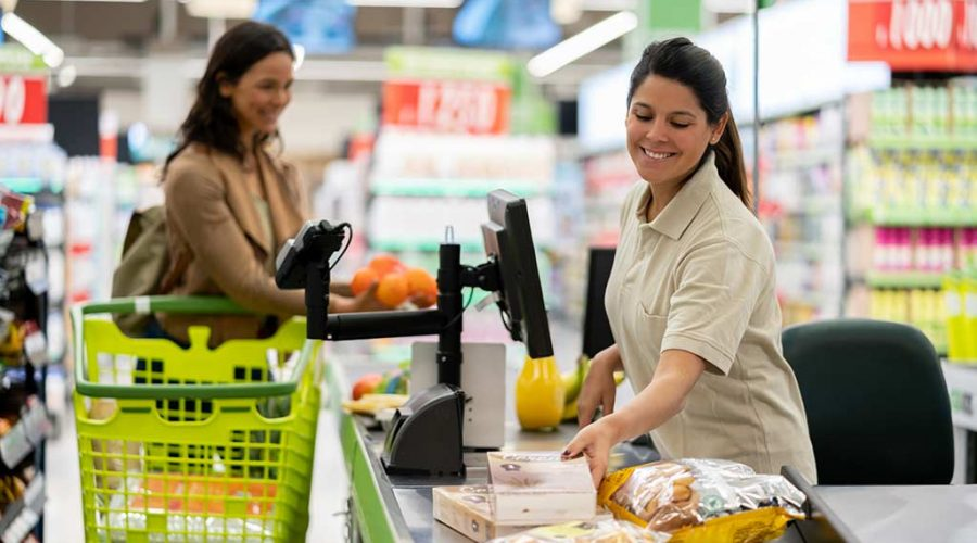 Friendly beautiful cashier registering products while talking to female customer at checkout in a supermarket both smiling