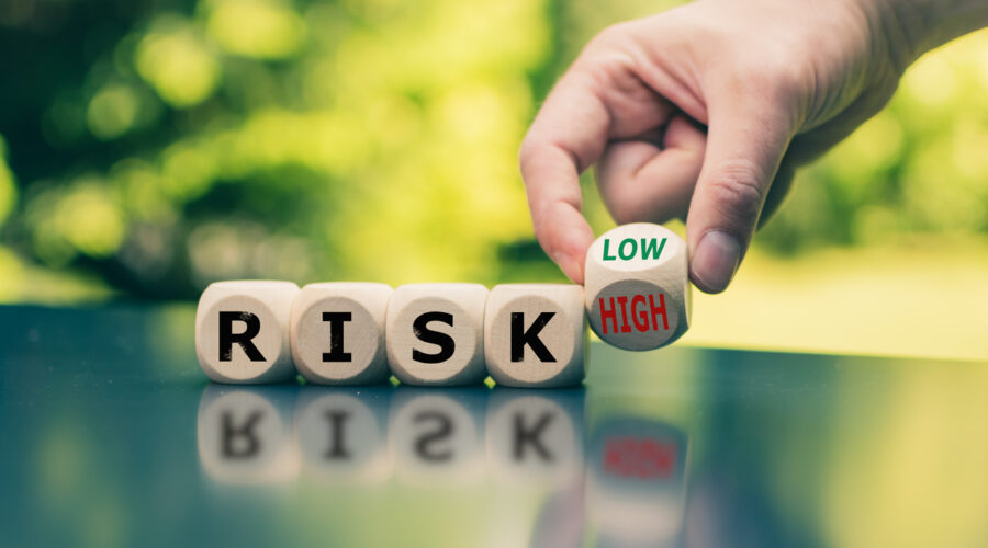 "Symbol for reducing a risk. Cubes form the word ""RISK"" while a hand turns a cube and changes the word ""high"" to low"" (or vice versa)."